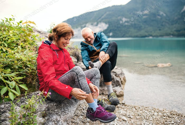 Senior pensioner couple hikers standing by lake in nature, taking shoes off.