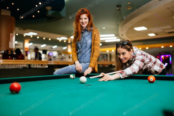 Beautiful women playing billiards