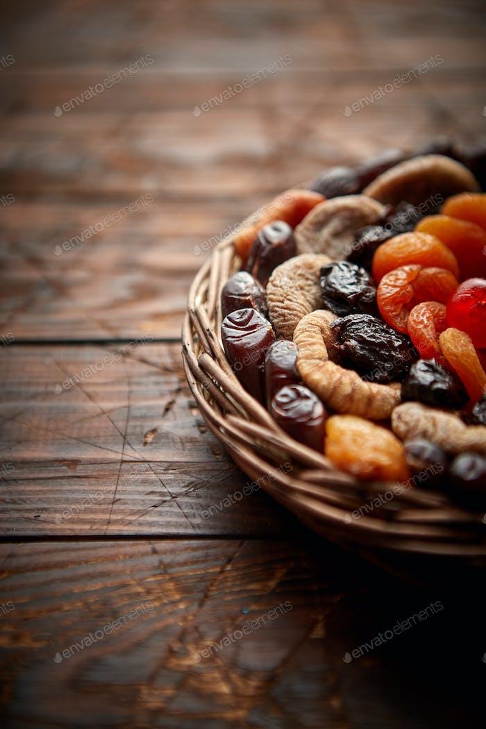 Mischung von getrockneten Früchten in einem kleinen Weidenkorb auf Holztisch