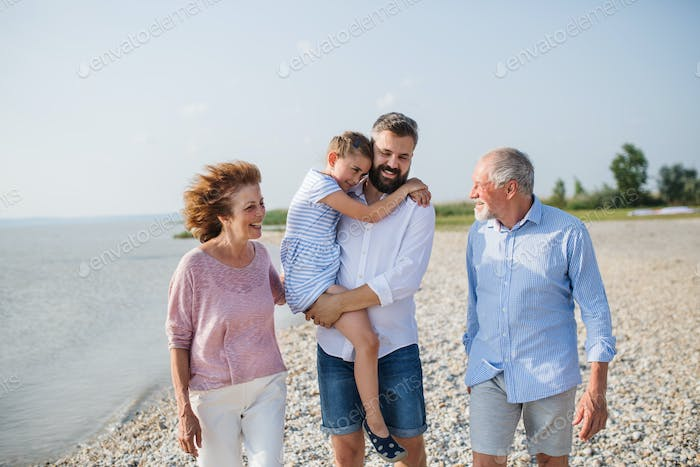 Multigeneration family on a holiday walking by the lake, talking