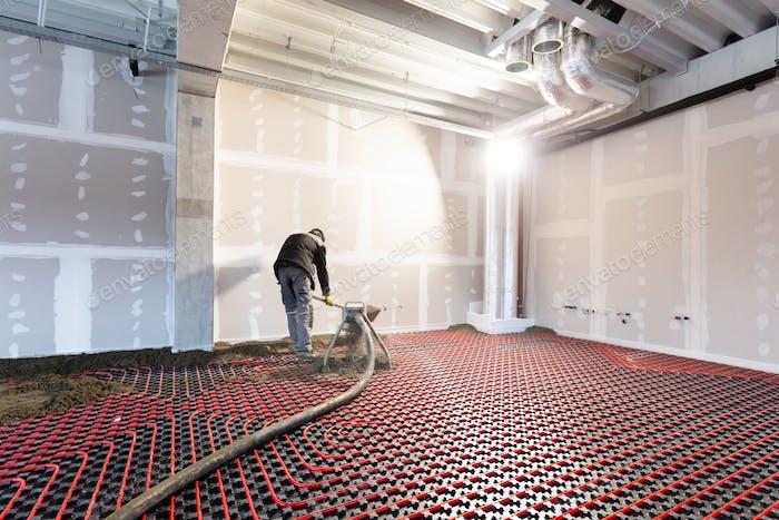 Worker installing floor heating in a new building