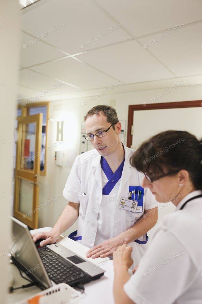 Doctor and nurse using laptop in corridor of hospital