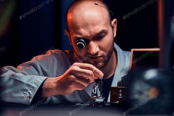 Fokussierter Mann arbeitet in seiner Werkstatt mit Monokel und anderen Werkzeugen, die alte Uhren reparieren
