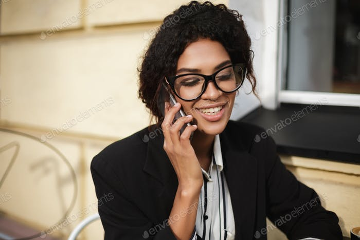 Beautiful African American girl in glasses sitting at the table of cafe and talking on her cellphone