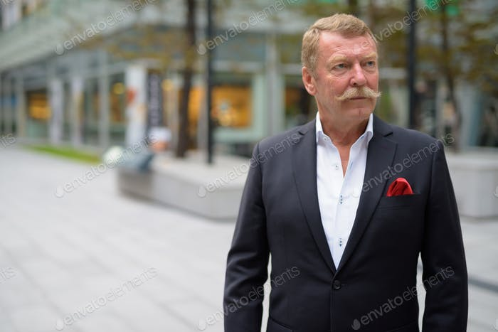 Handsome senior businessman with mustache exploring the city