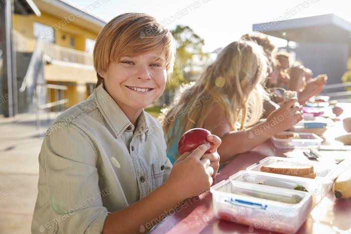 Junge in der Grundschule Mittagessen Tisch lächelnd Kamera
