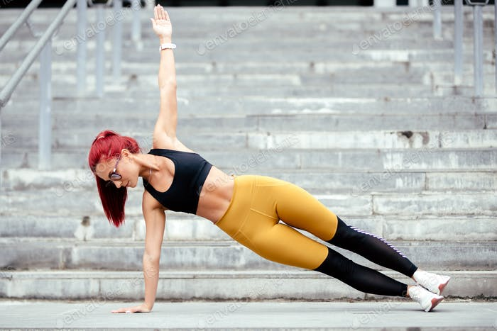 Athletic woman doing sports training, side planks and jogging outdoors
