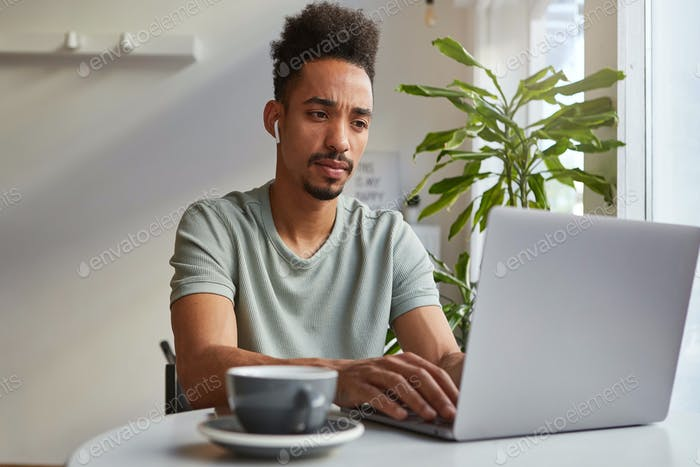 Young attractive African American pensive boy, sits at a table in a cafe, works at a laptop
