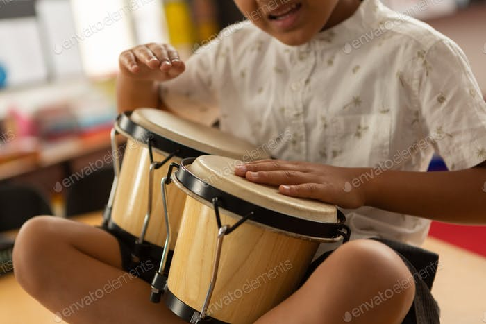 Mid section of smiling mixed-race schoolboy playing bongo in a classroom at elementary school