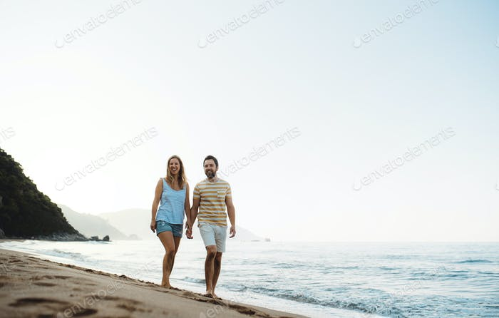 A cheerful man and woman walking on beach on summer holiday. Copy space.