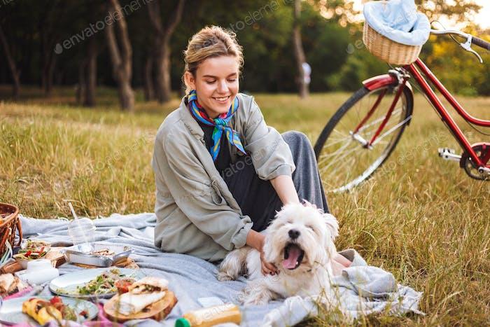Buena chica sonriente con lindo perro felizmente pasar Tiempo en beautif