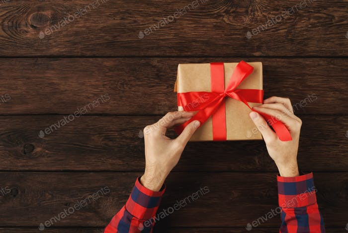 Man opening present on wooden background