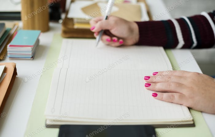 Woman hand holding pen work on blank notepad page