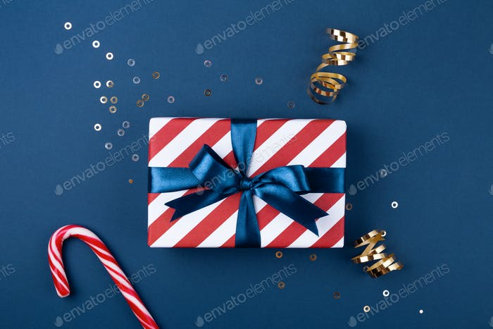 Gift Box Wrapped in Red Striped Paper and Tied with Blue Ribbon Decorated with Confetti.