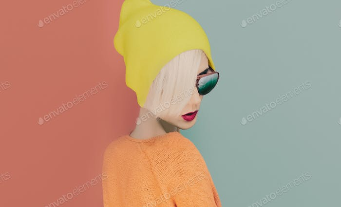 blond girl with stylish cap and sunglasses on colored background