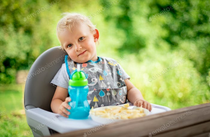 Cute baby sitting in high chair at the dinning table outdoor