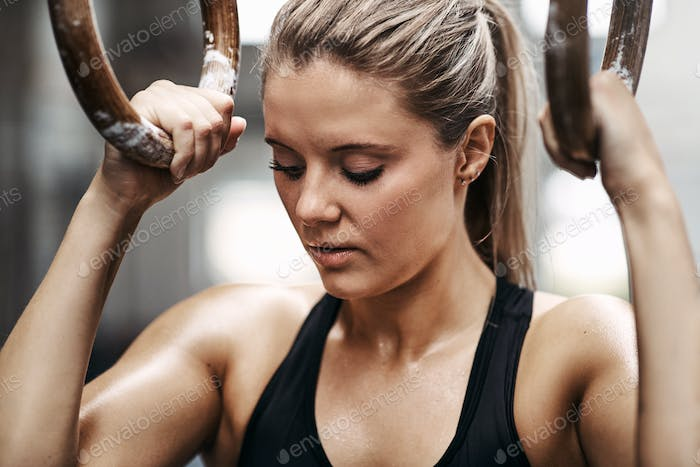 Fit young woman exercising on rings at the gym