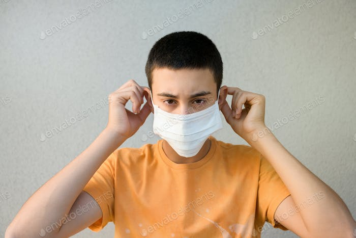 Young man putting on a surgical face mask