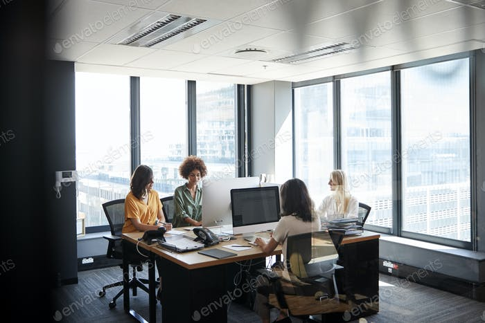 Four female creative colleagues working together in an office, seen through glass wall
