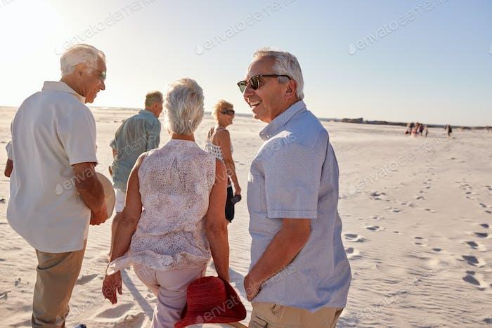 Grupo de Amigos mayores caminando a lo largo de arena Playa en verano Grupo vacaciones