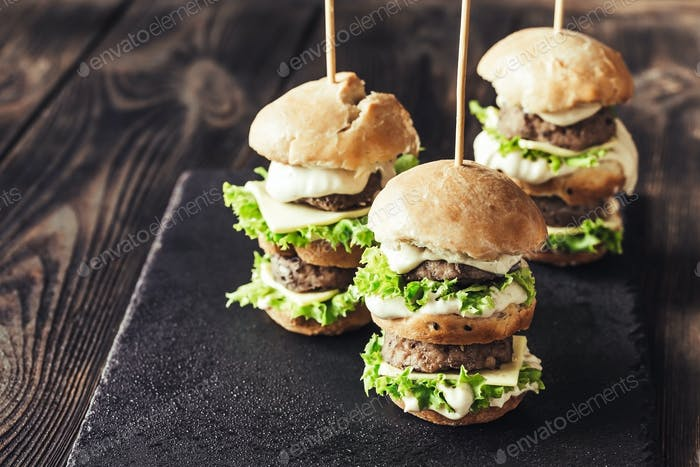 Burgers on the black stone board