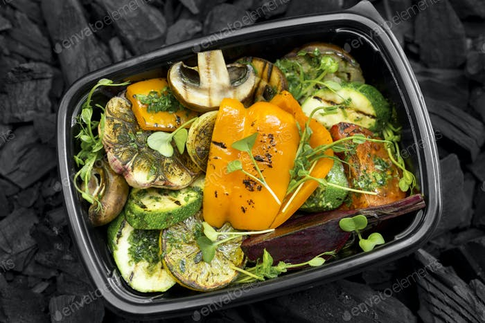 Freshly grilled healthy vegetables in to go black box on charcoal