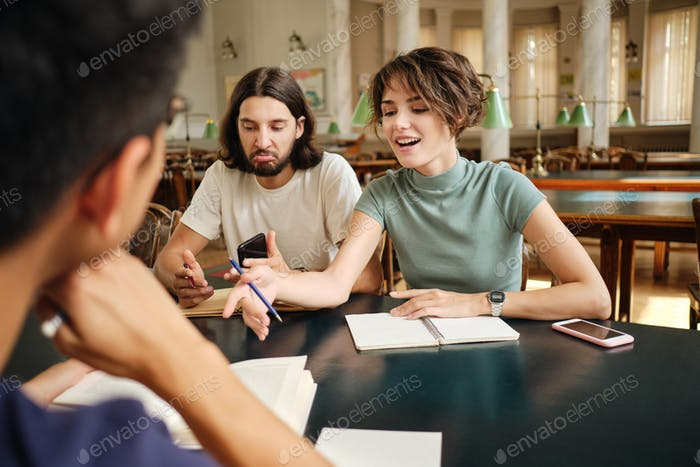 Attractive casual students emotionally discussing study project together in library of university