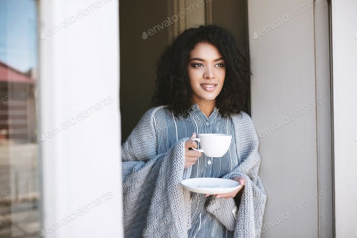 Portrait of beautiful lady with dark curly hair leaning on door with cup of coffee in hands