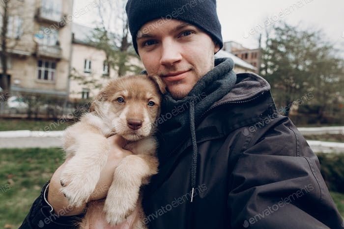 man taking selfie with adorable brown puppy with amazing blue eyes