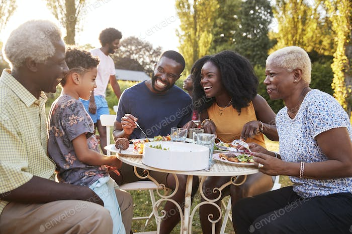 Black multi generation family eating at a table in garden