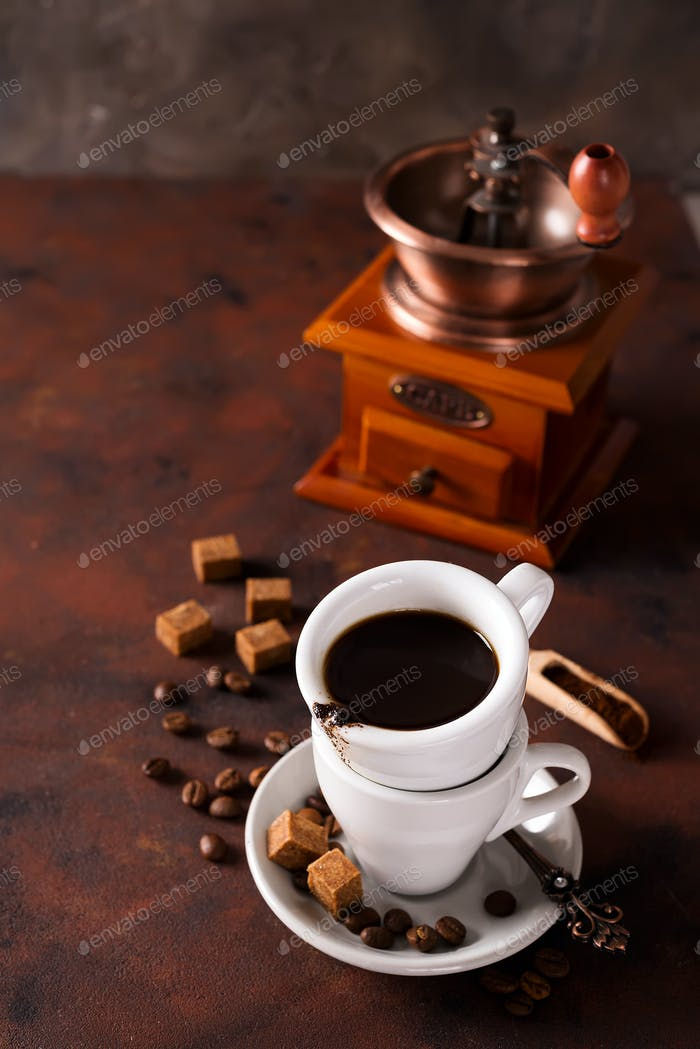 Cup of steaming hot coffee with coffee beans, coffee grinder, and coffee beans bag