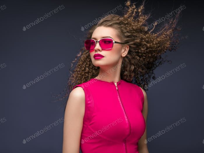 Attractive woman in red sunglasses emotional portrait fashion female with long beautiful curly hair