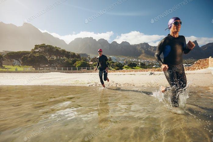 Triathlon participants running in the water