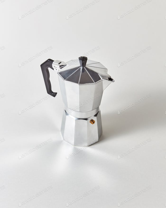 Traditional metal Italian coffee maker presented on a gray background with copy space