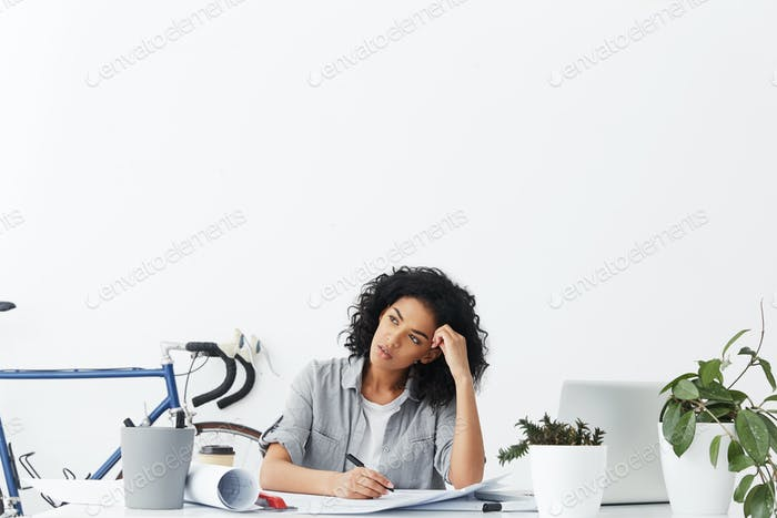 Portrait of attractive mixed race woman architect with black curly hair reclining on her desk with b