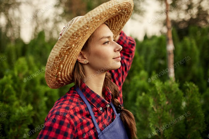 Charming girl gardener in a straw hat stands in the nursery-garden with a lot of thujas on a warm