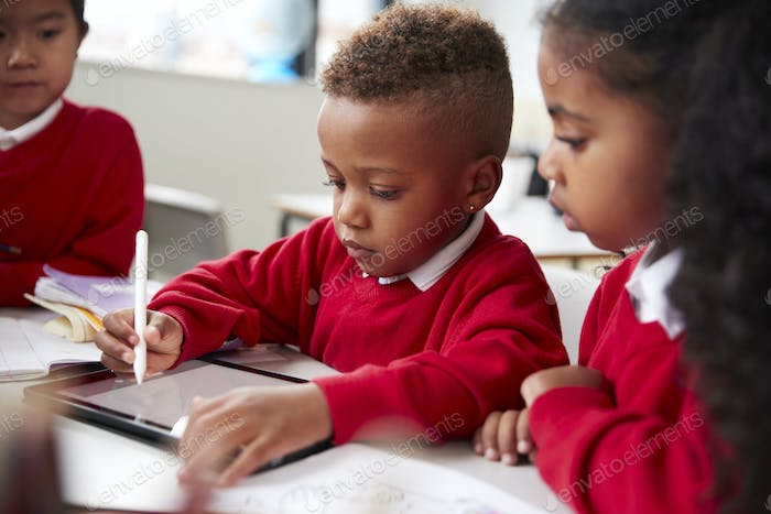 Three kindergarten school kids sitting at desk in a classroom using a tablet computer