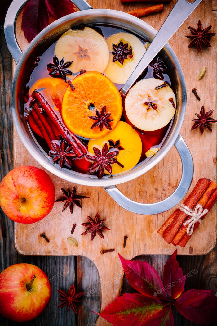 Heißes Glühwein Getränk mit Zitrusfrüchten, Äpfeln, Zimtstangen, Nelken und Anis in der Pfanne
