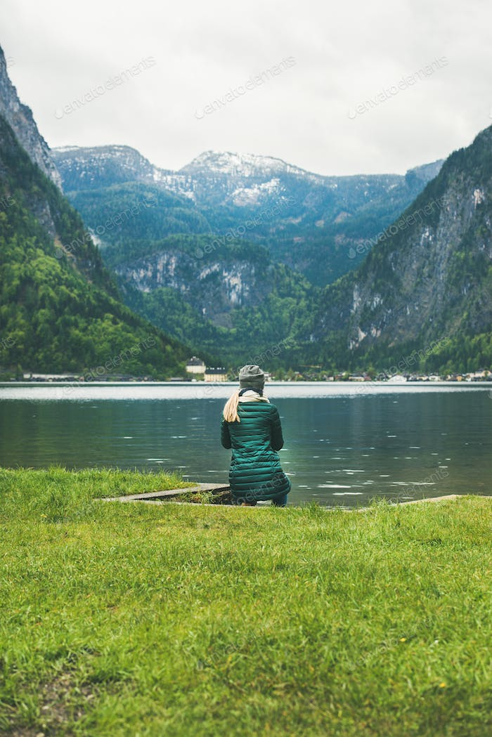 Female traveller sitting at mountain lake coast in the Alps