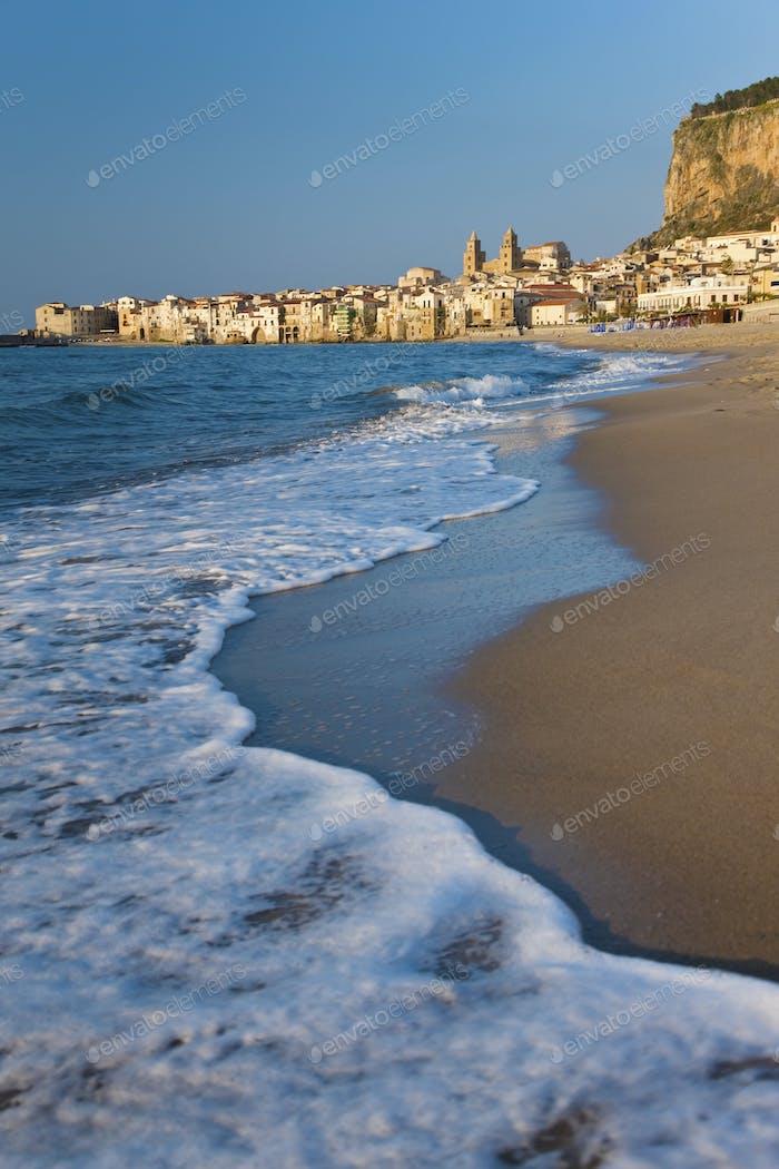 Blick entlang der Küste mit Sandstrand, Stadt in der Ferne.
