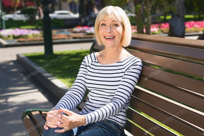 Happy senior woman relaxing on park bench