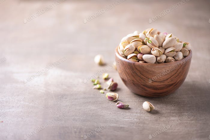 Green pistachio nuts in wooden bowl on wood textured background. Copy space. Superfood, vegan