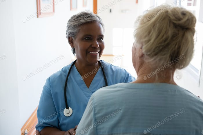 Senior woman and nurse talking while standing in corridor
