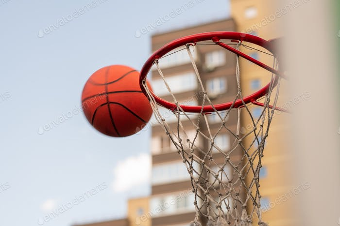 Ball for playing basketball thrown by player close to basket
