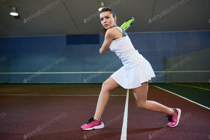 Energetic Young Woman Playing Tennis