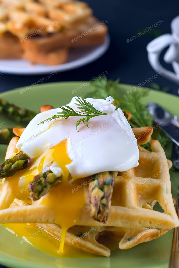 Grilled waffle with Green boiled Asparagus with Poached Egg, with salt and spices on ceramic plate