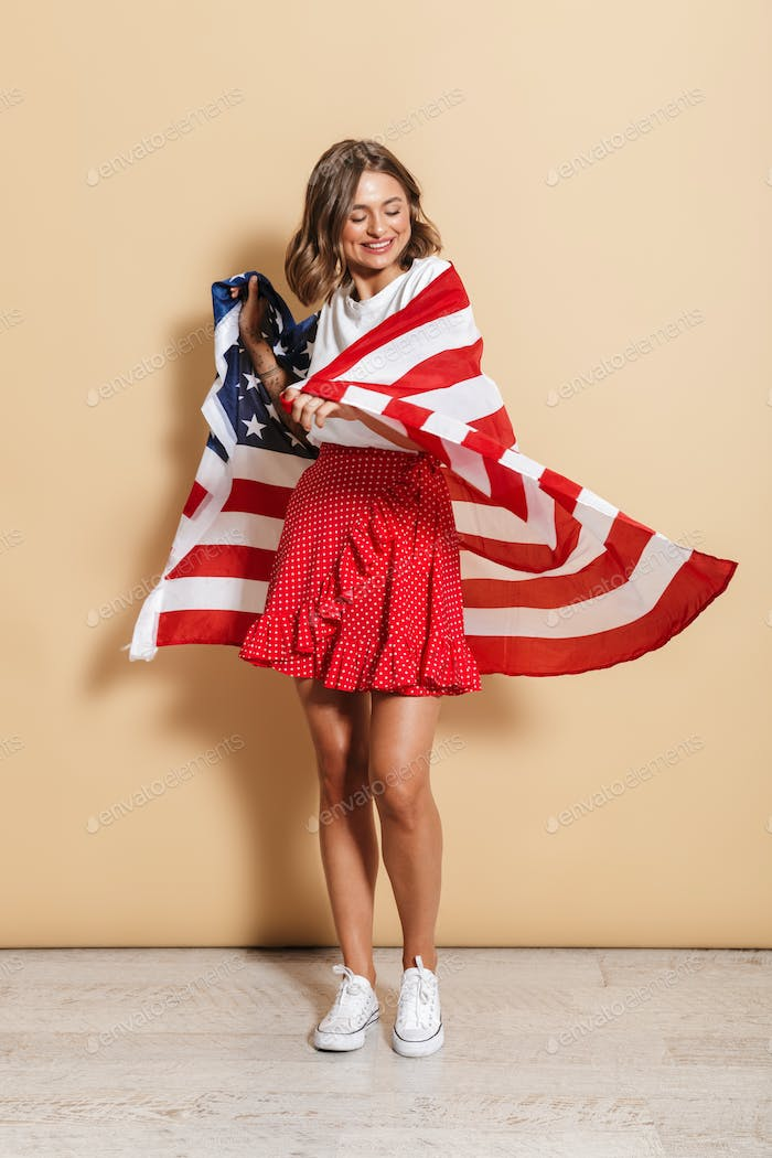 Photo of elegant young woman wearing american flag standing and smiling