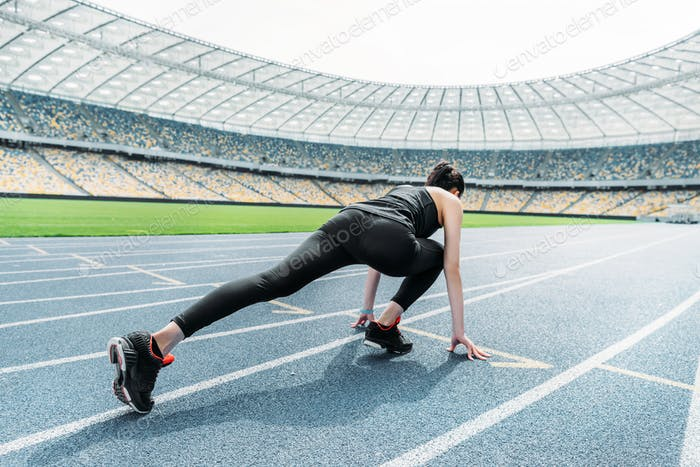 Young fitness woman in sportswear in starting position on stadium