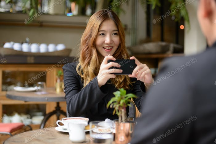 Happy young Asian business couple together at the coffee shop with woman taking picture using phone