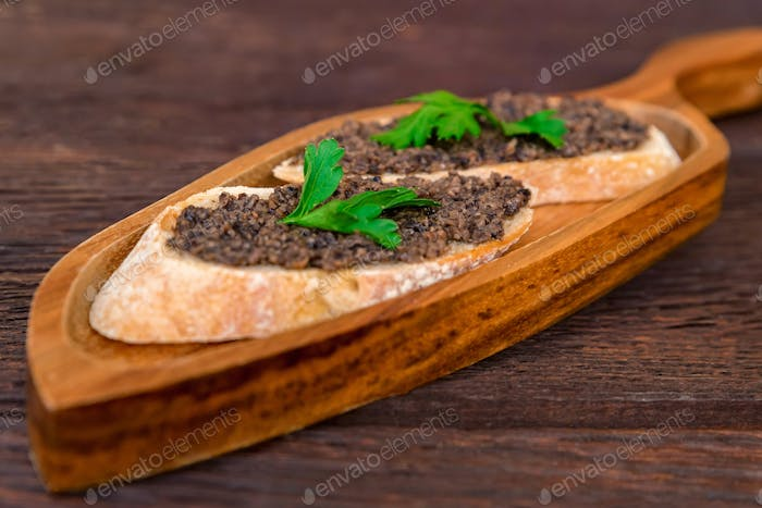 Fresh tasty bruschetta with truffle sauce and parsley